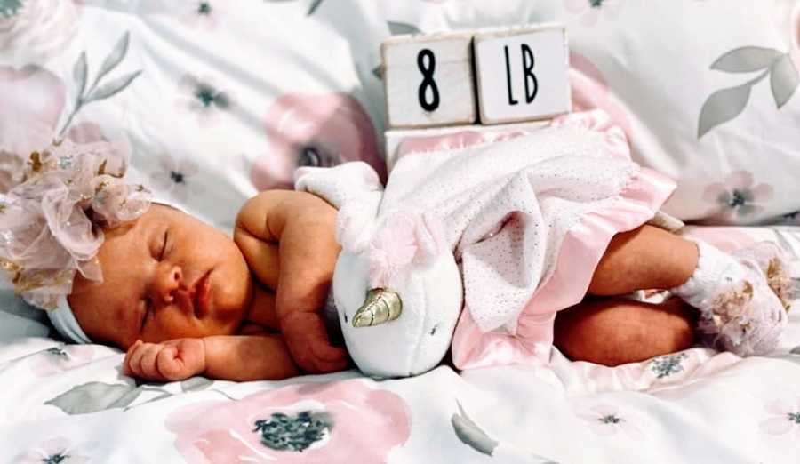 A newborn baby girl lying next to a marker that says 8lb