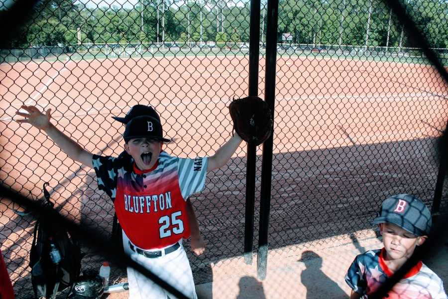 A little boy cheers from inside the dugout