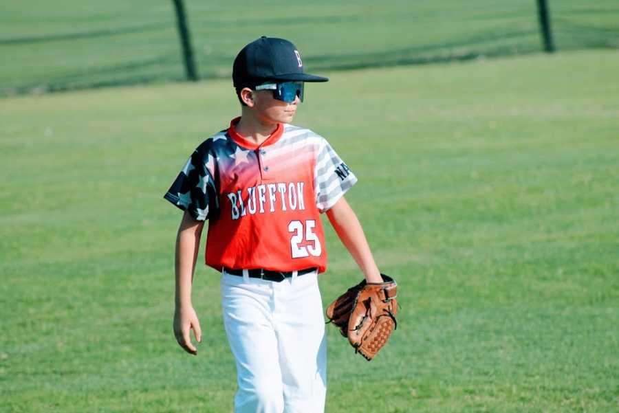 A boy wearing his all-star baseball jersey