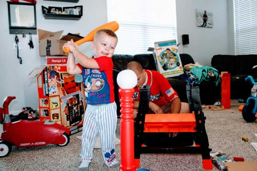 A little boy plays baseball indoors with a plastic toy bat and tee