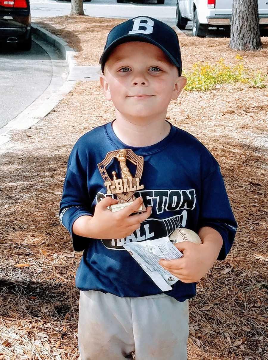 A little boy holds a t-ball trophy and a baseball