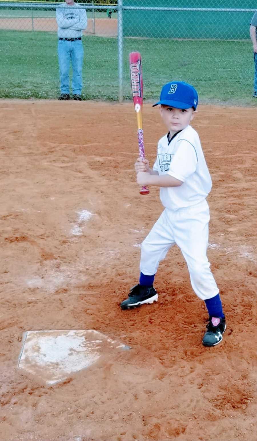 A little boy stands at home plate holding a bat