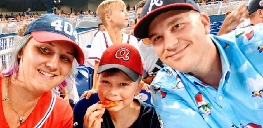 Parents sit with their son at a baseball game
