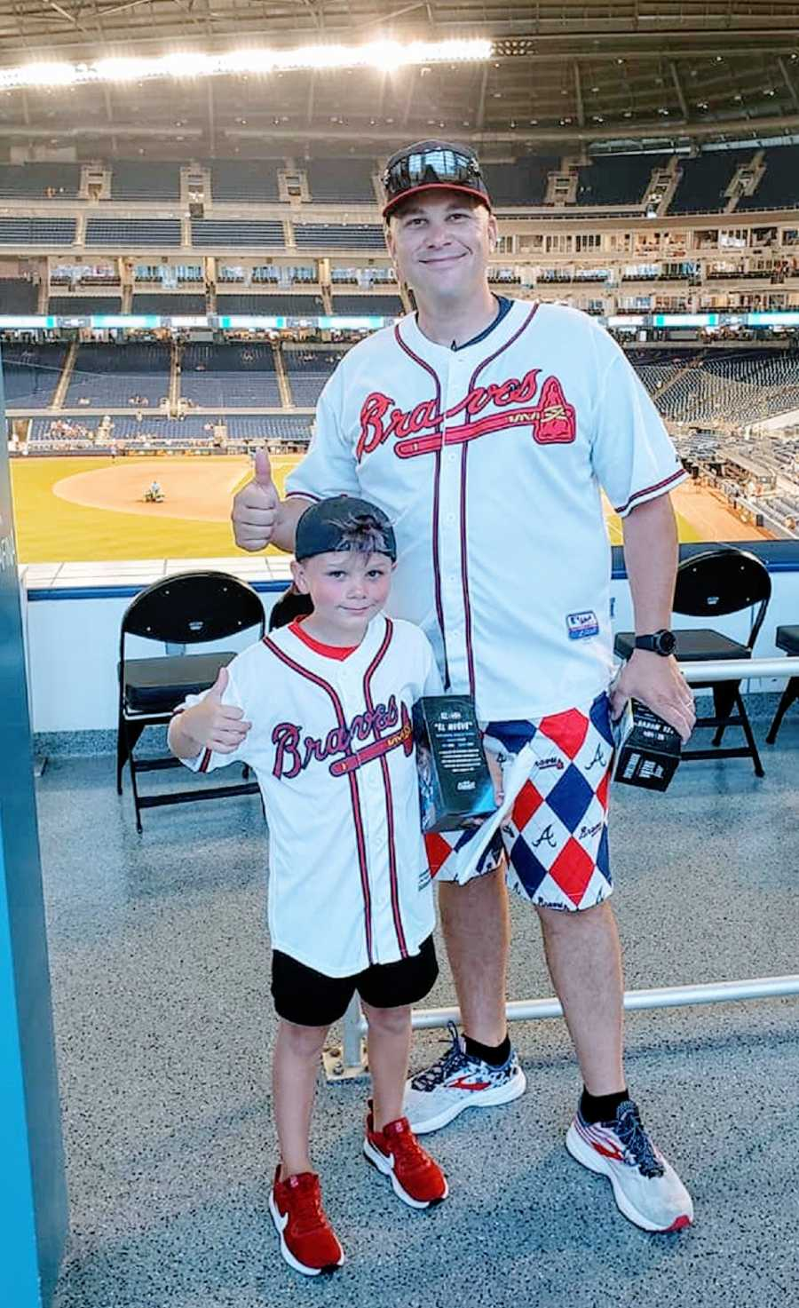 A boy and his father wearing Braves jerseys at a baseball game