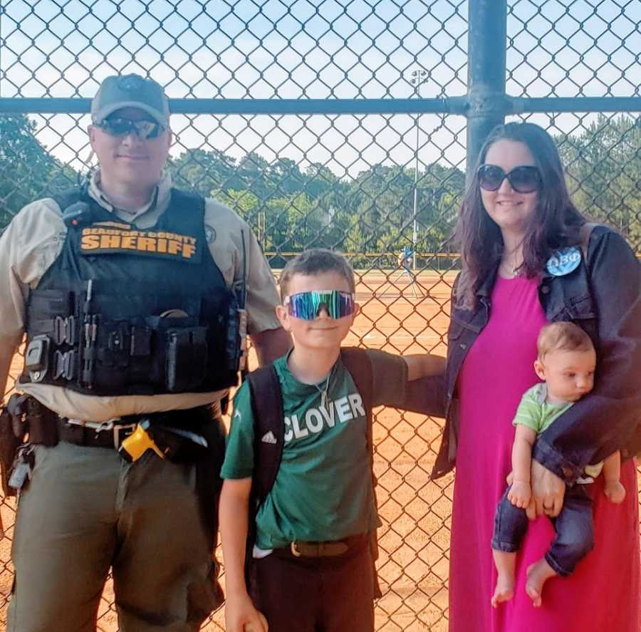 A boy stands with his parents and his little brother at a baseball field