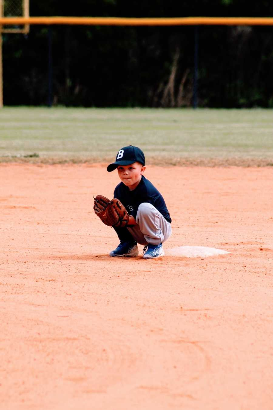 A little boy squats by the base while playing t-ball