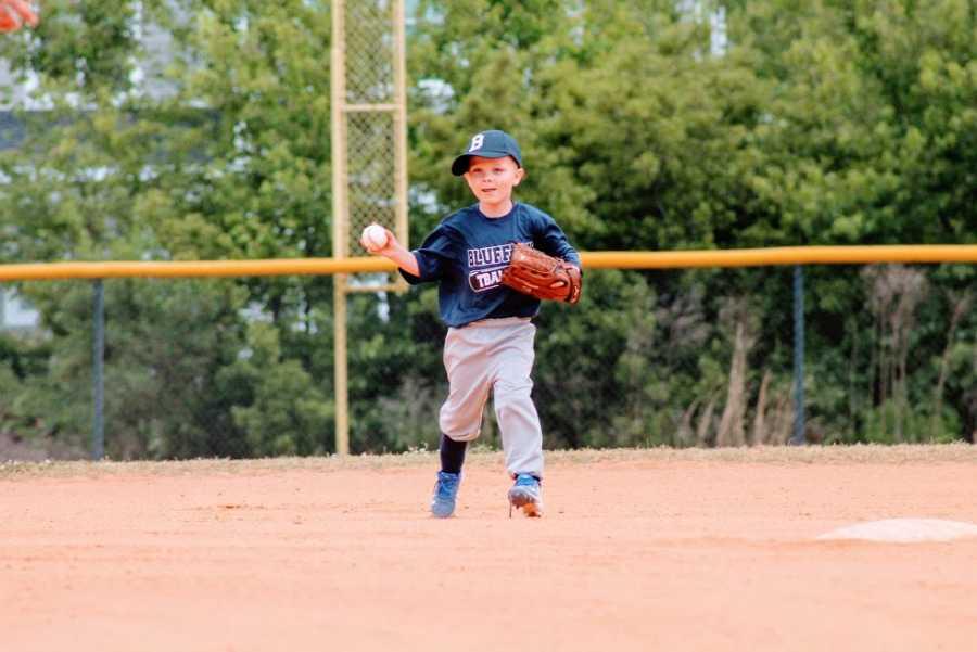 A little boy fields a ball in a t-ball game