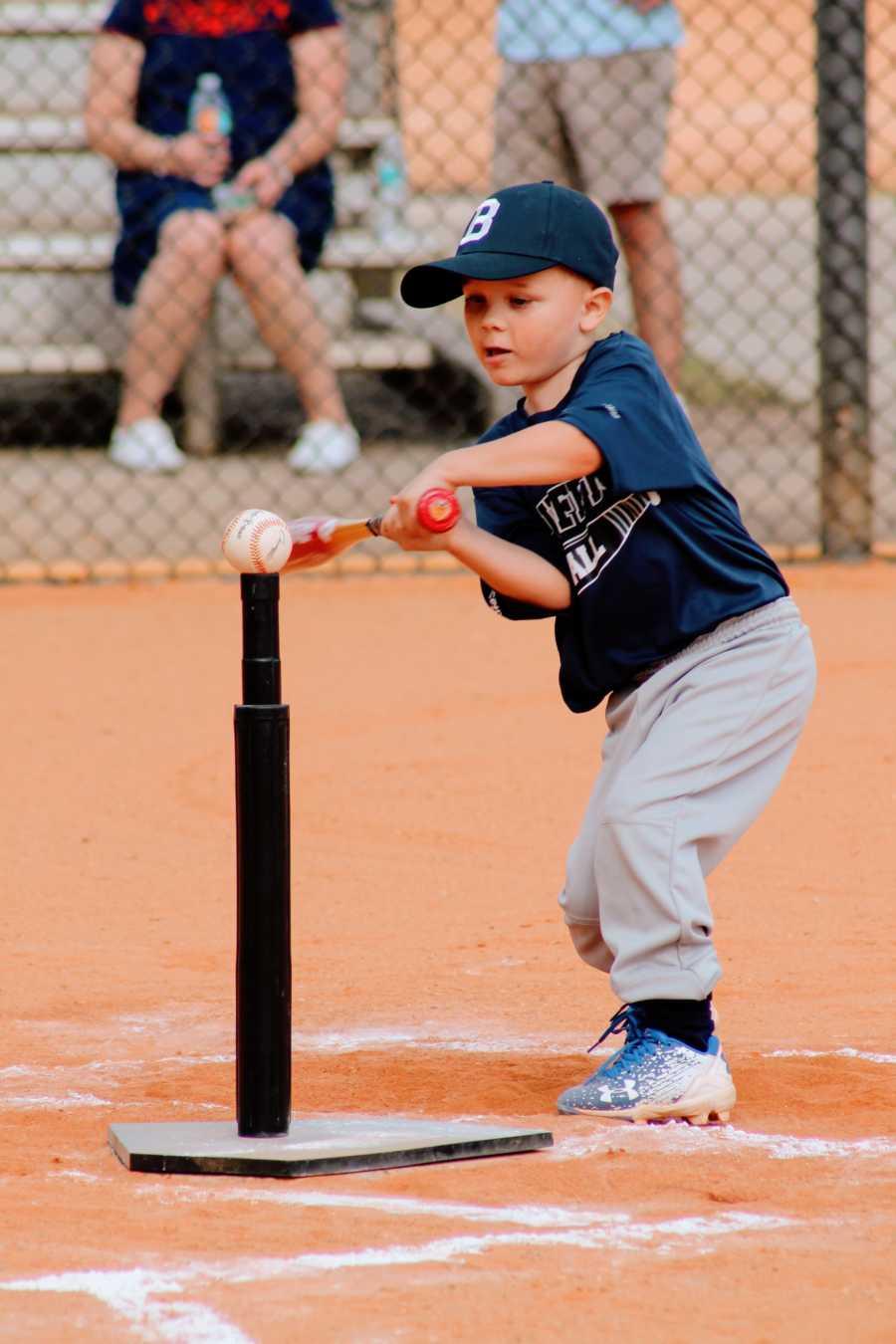 A little boy swings a bat at a ball on a tee