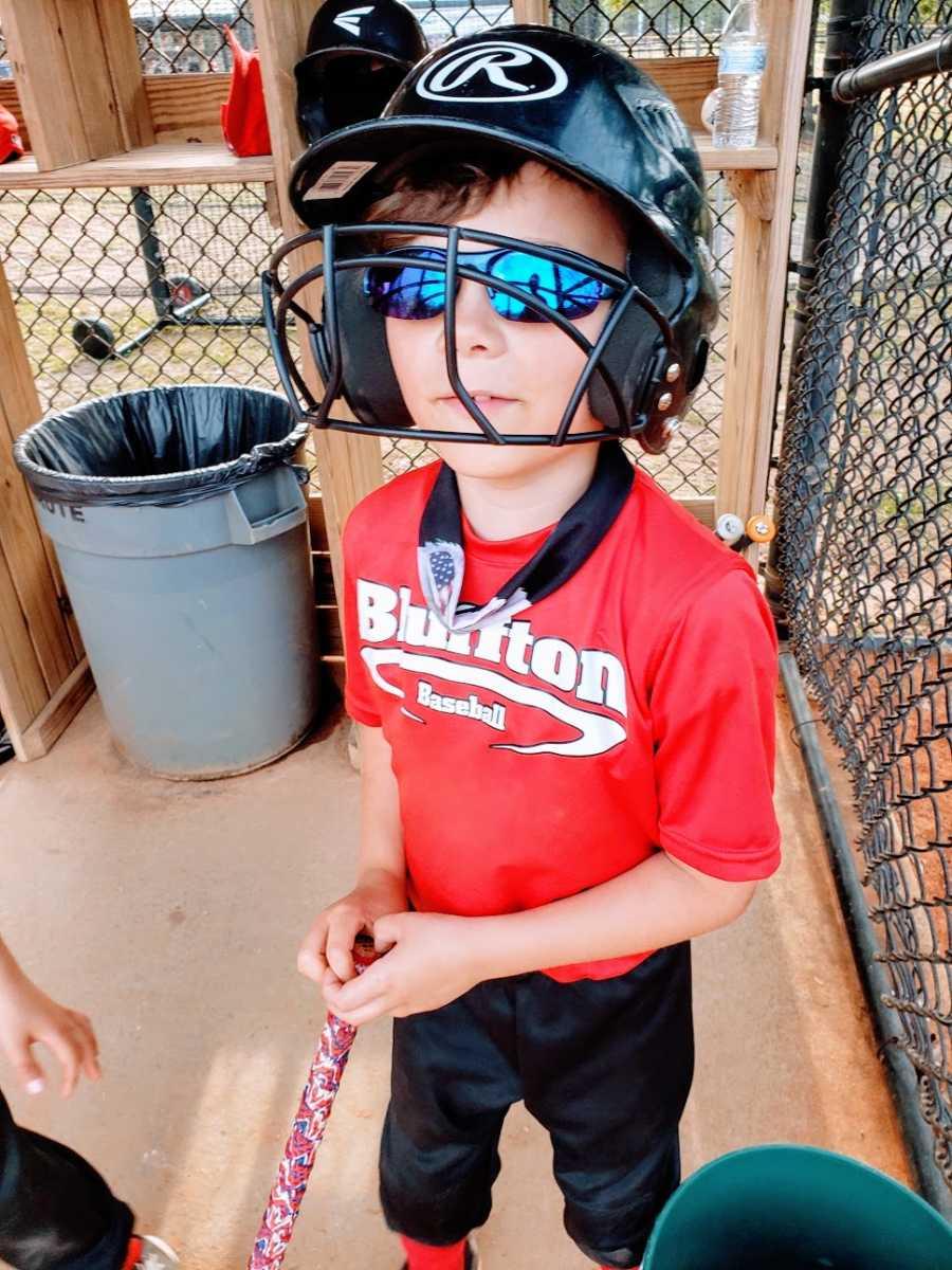 A boy wearing a batting helmet stands in a dugout