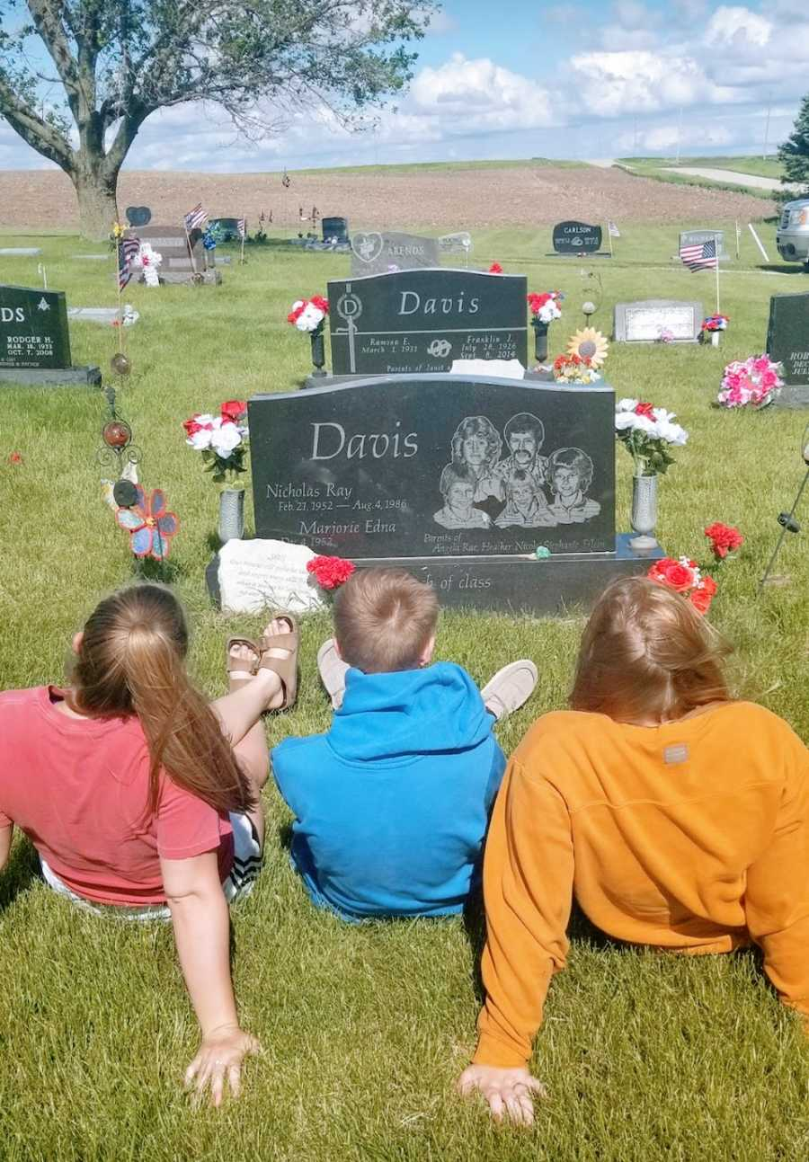 Three children sit in a graveyard looking at a headstone
