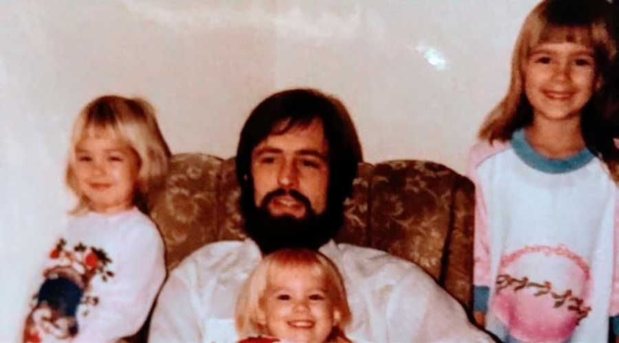 A father sits with his three young daughters