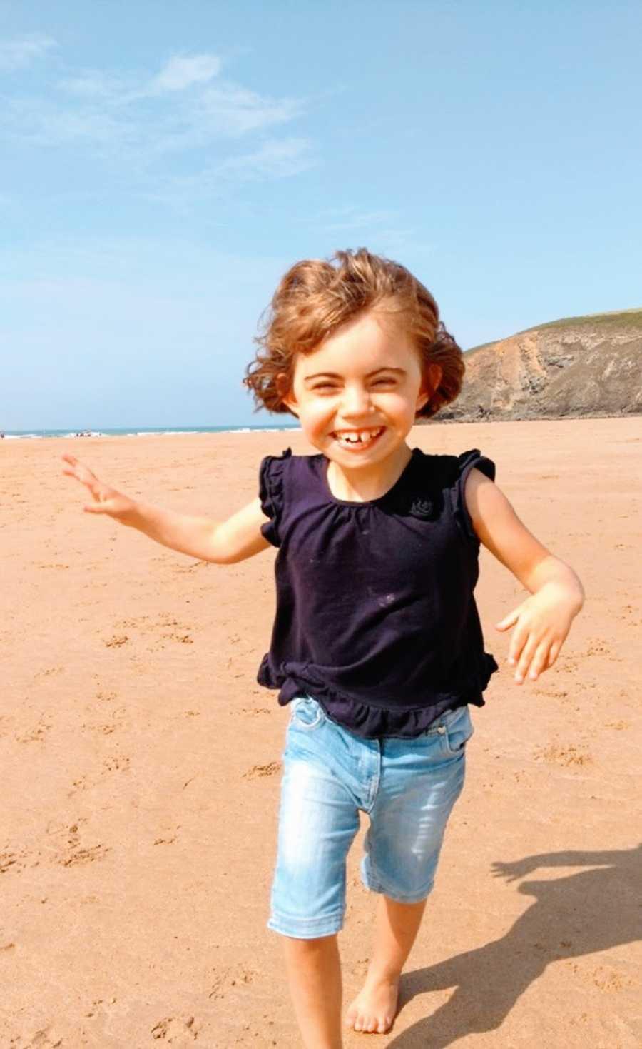A young girl runs on a beach