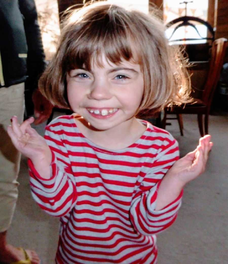 A girl wearing a striped shirt shrugs and giggles