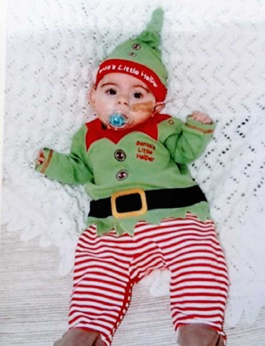 A baby girl in an elf costume lies in a crib