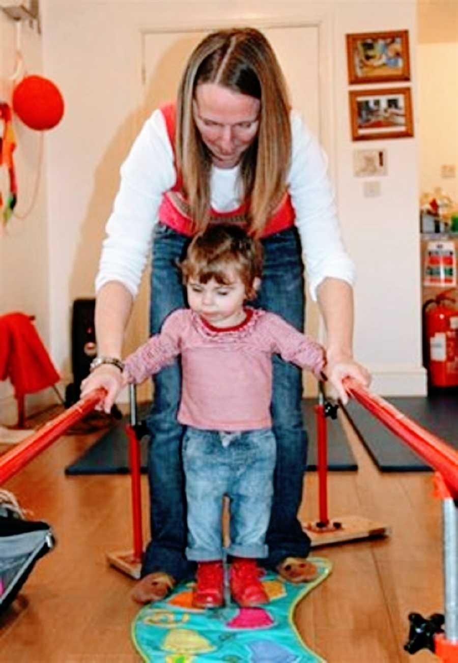 A little girl learns to walk at therapy