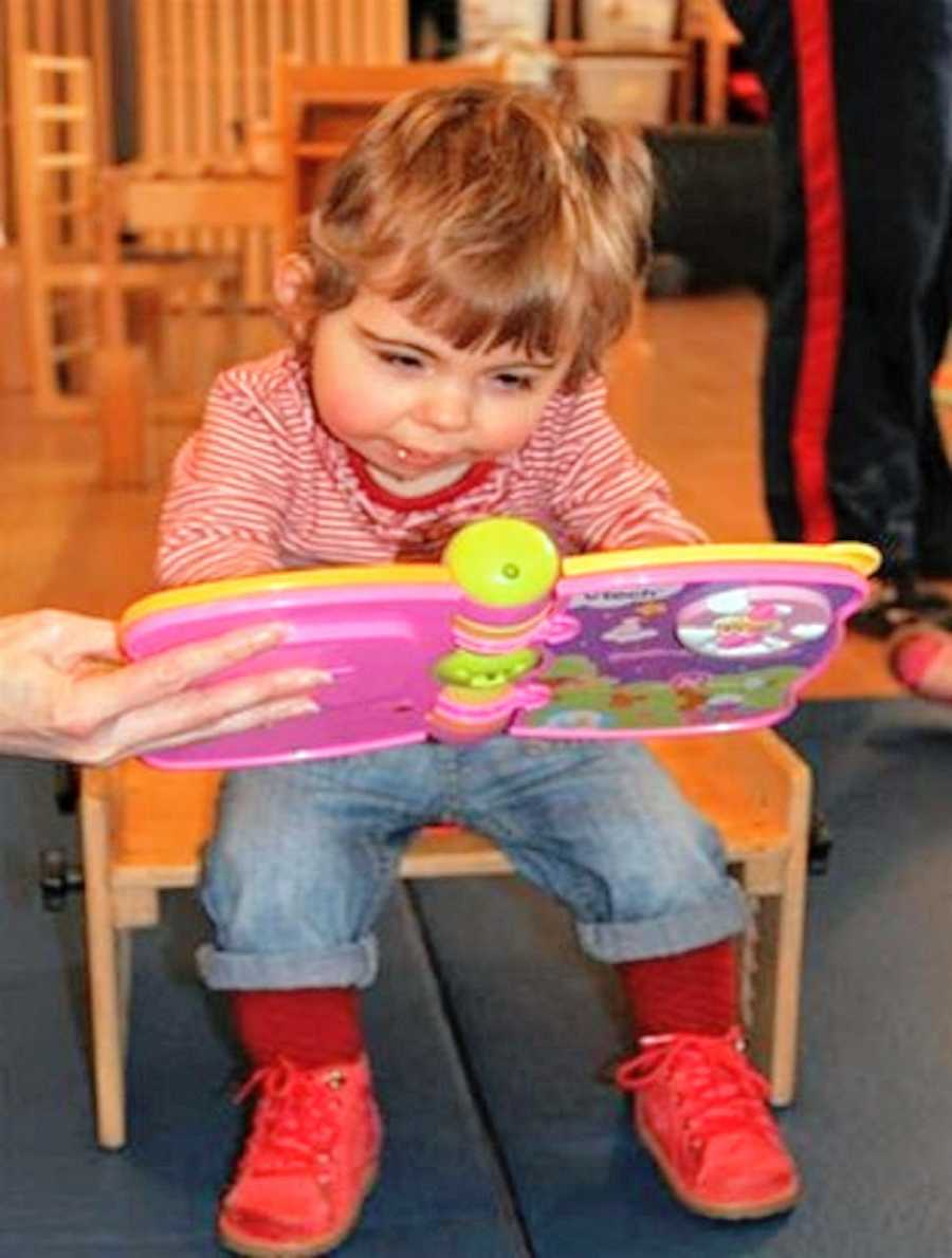 A little girl sits and plays with a toy book