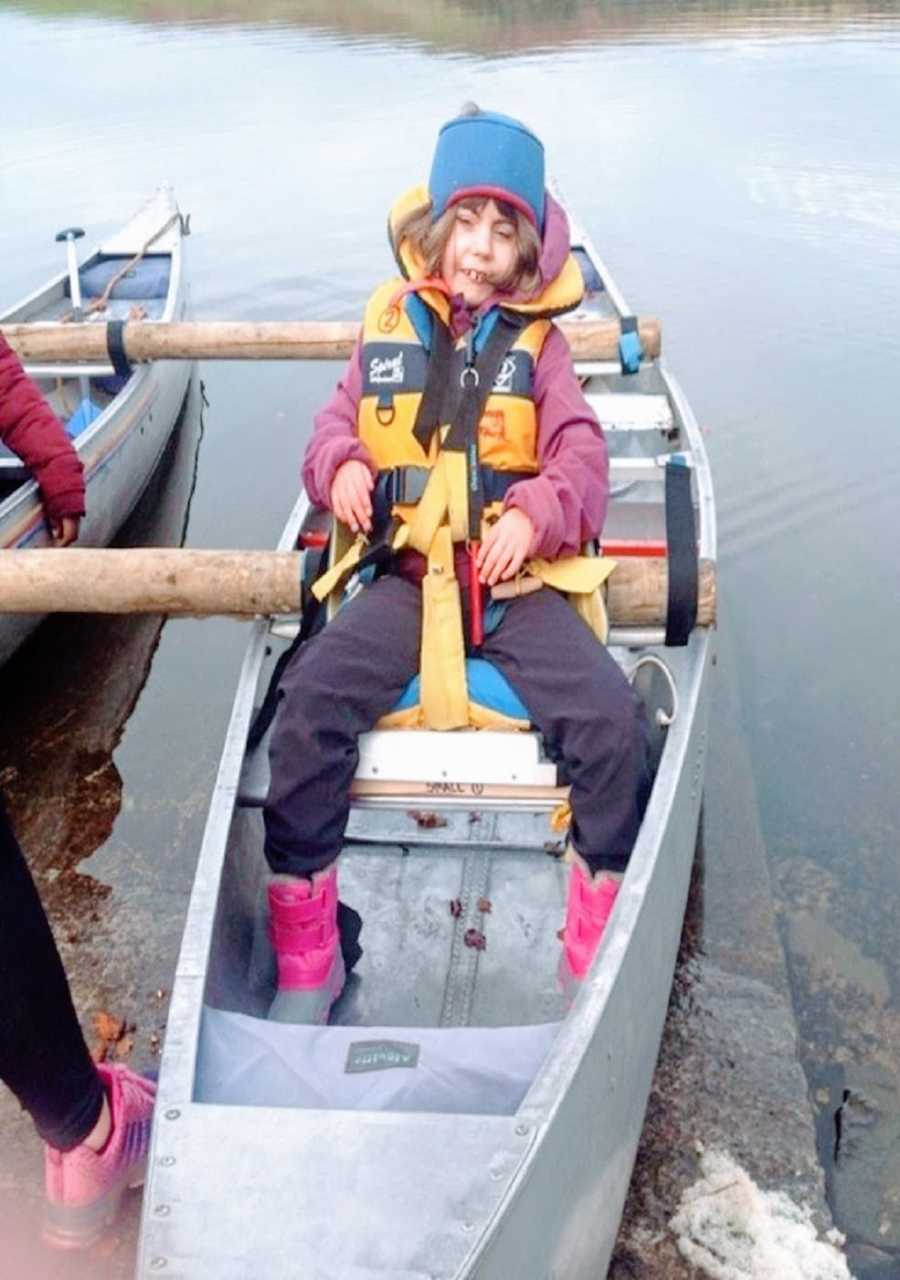 A girl with CdLS sits in a canoe