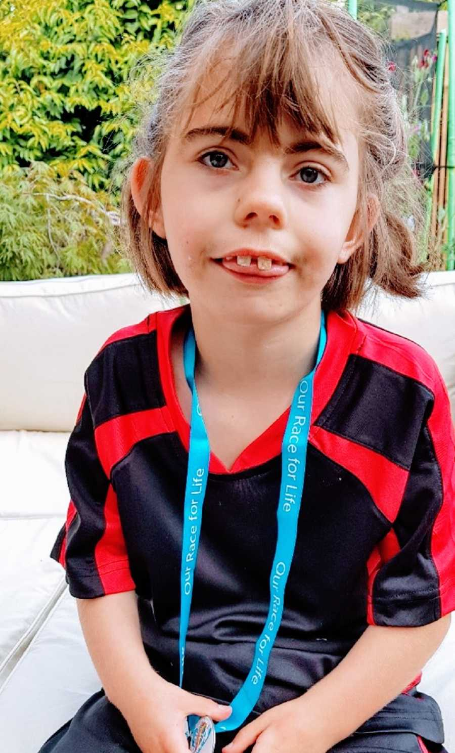 A girl wearing a lanyard sticks her tongue out at the camera
