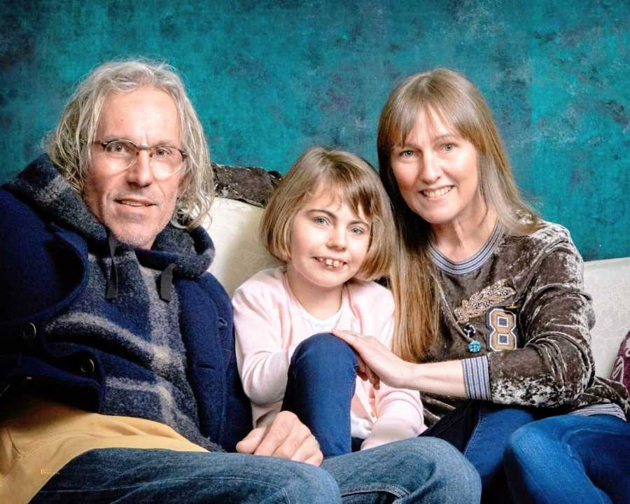 Parents sit with their daughter on a couch