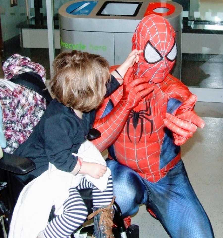 A little girl flicks at Spiderman's eye