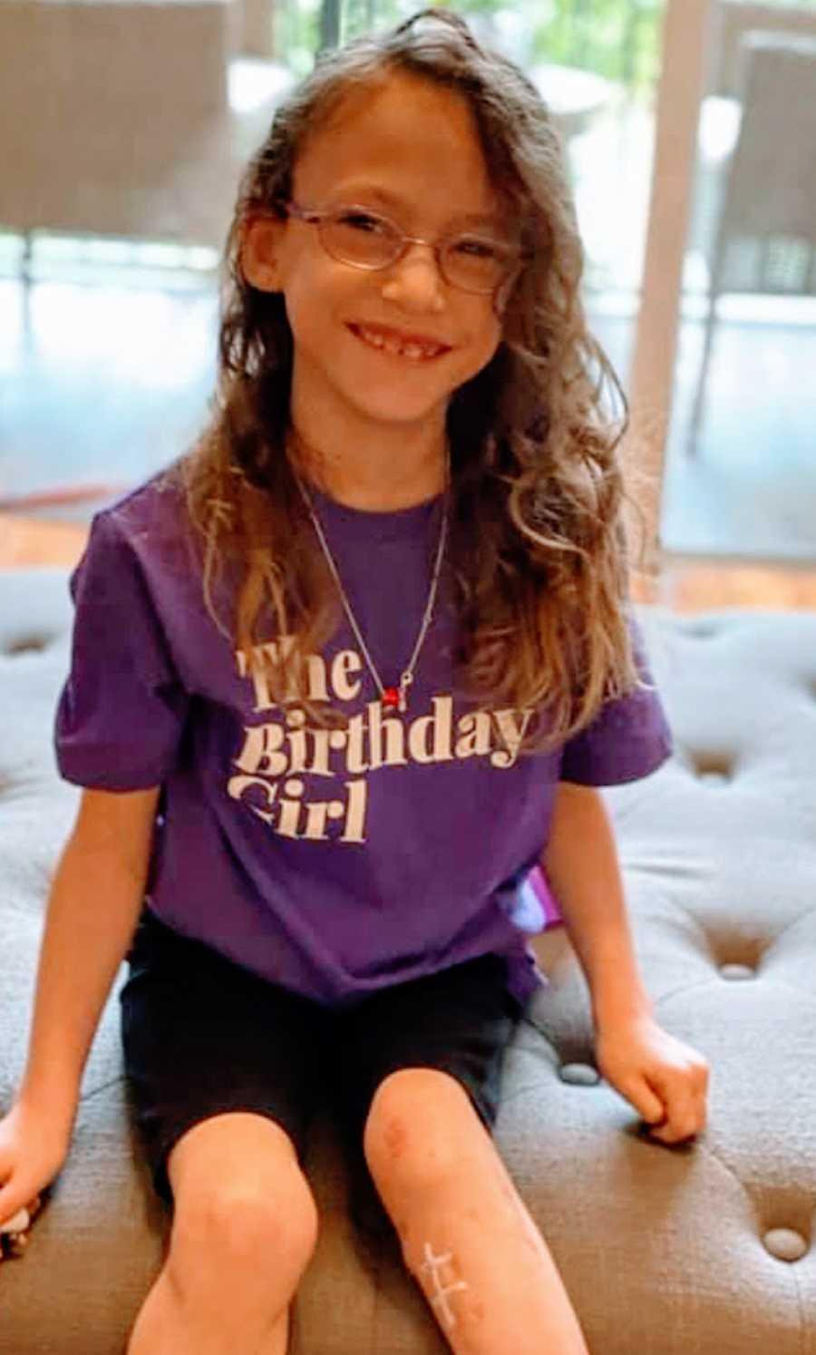 A young girl wearing a purple shirt