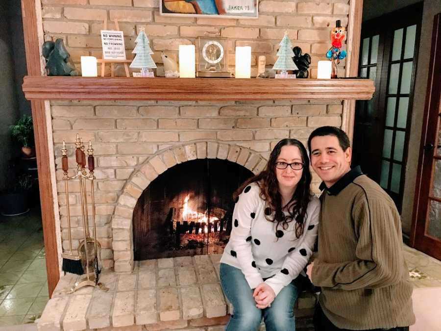 A woman sits with her partner at a fireplace