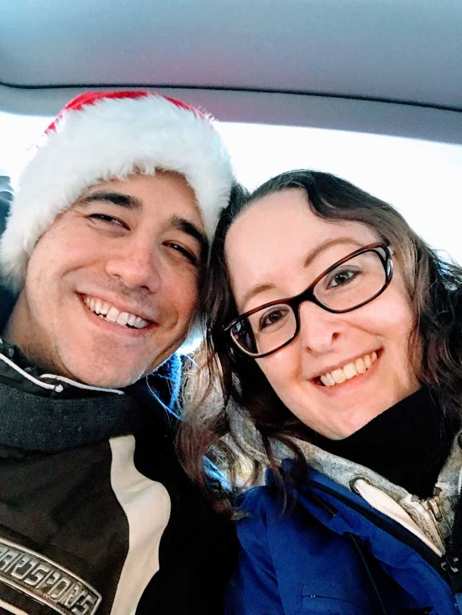 A woman and her partner who is wearing a Santa hat