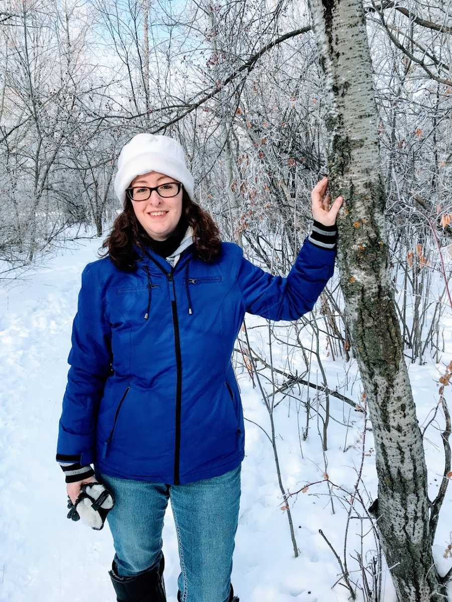A woman stands in the woods in the snow