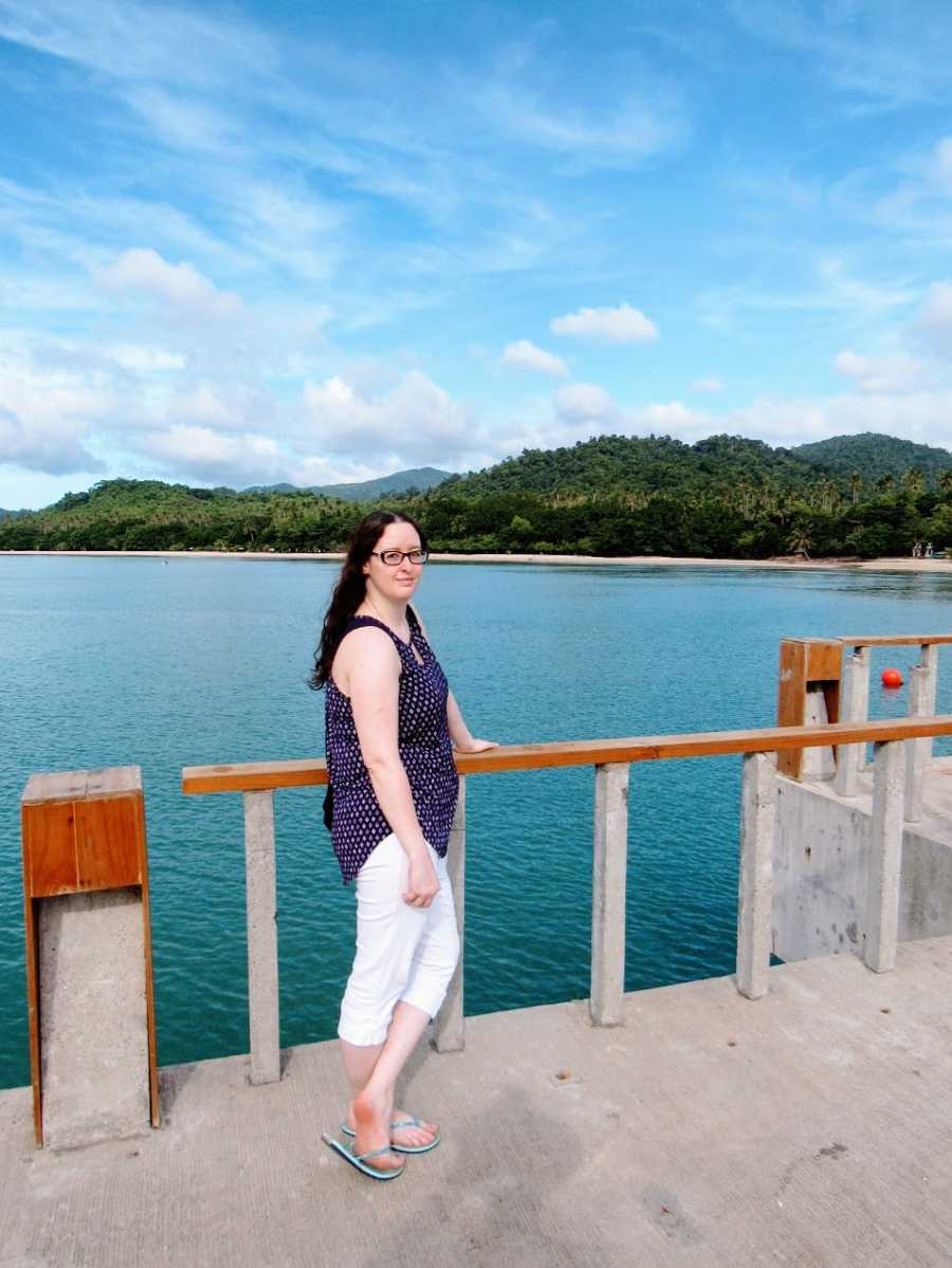 A woman stands by a railing near the water