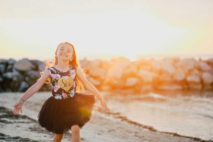 海滩上穿着黑色裙子的小女孩