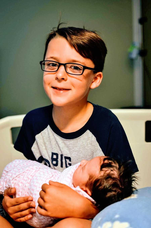 一个小男孩在医院抱着他刚出生的妹妹