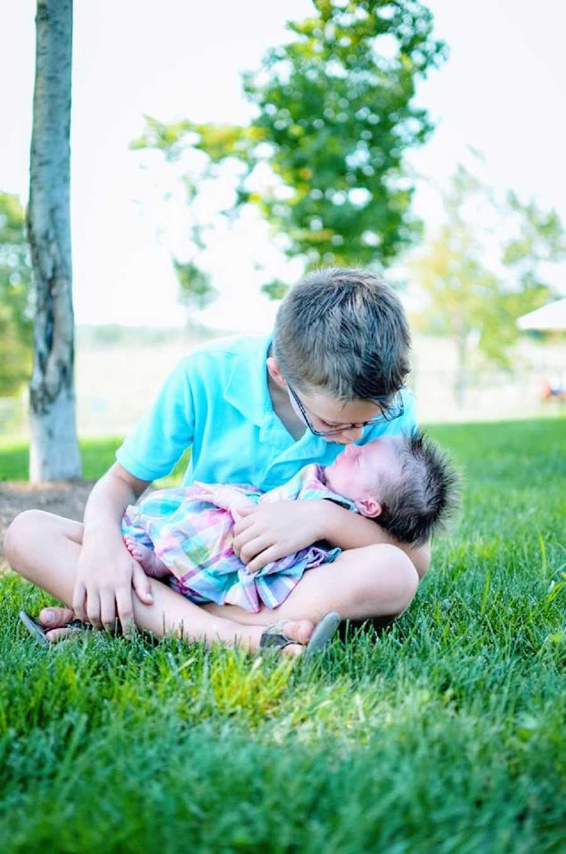 一个男孩吻了他的小妹妹的鼻子