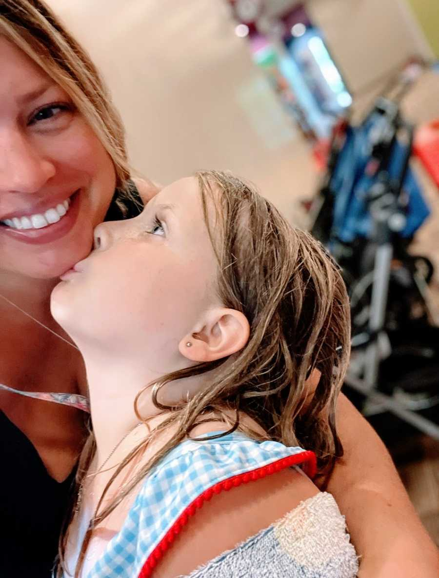A little girl kisses her mom on the chin