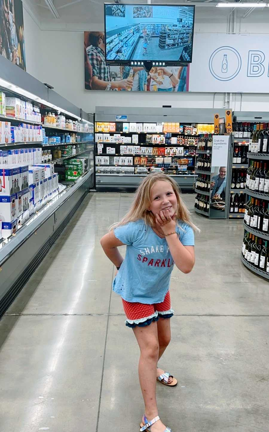 A little girl poses in the grocery store