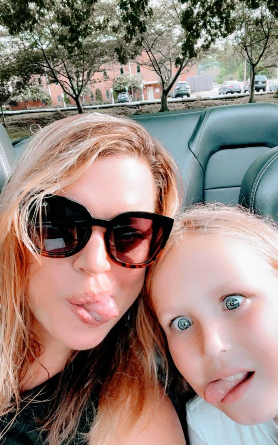 A mom and her daughter make silly faces in their car