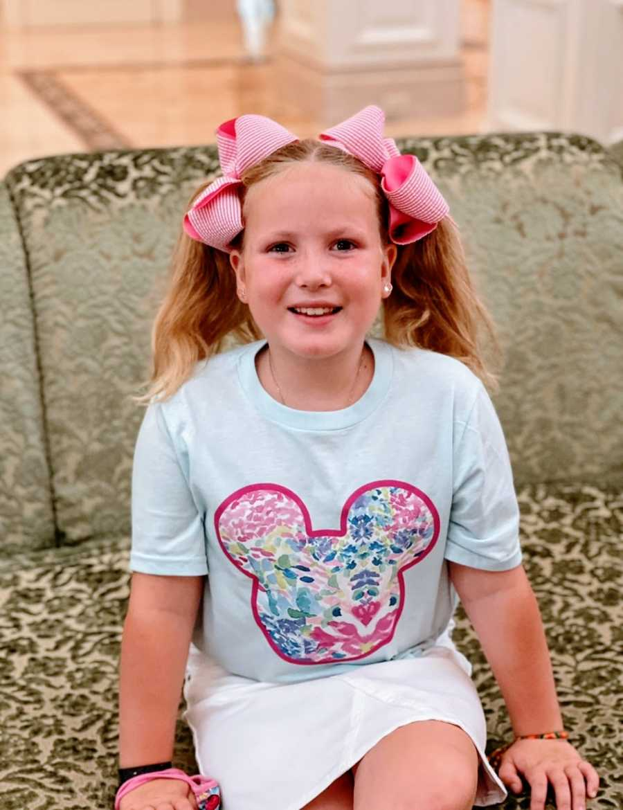 A little girl wearing bows in her hair and a Mickey Mouse shirt