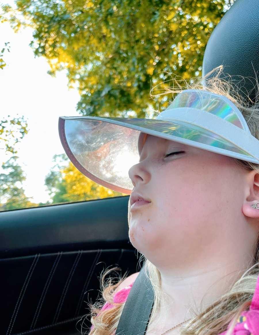 A little girl sleeps in a car while wearing a visor