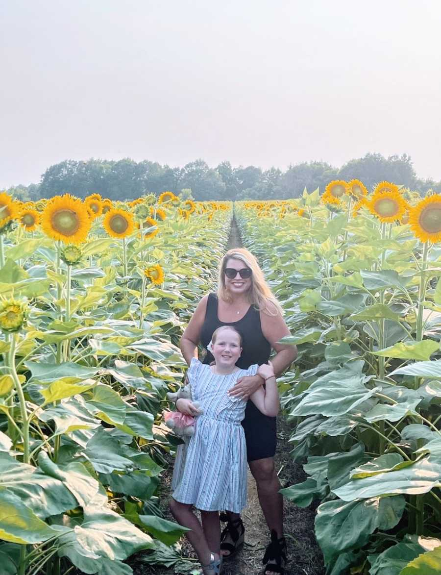 A mother and her daughter stand in a field of sunflowers