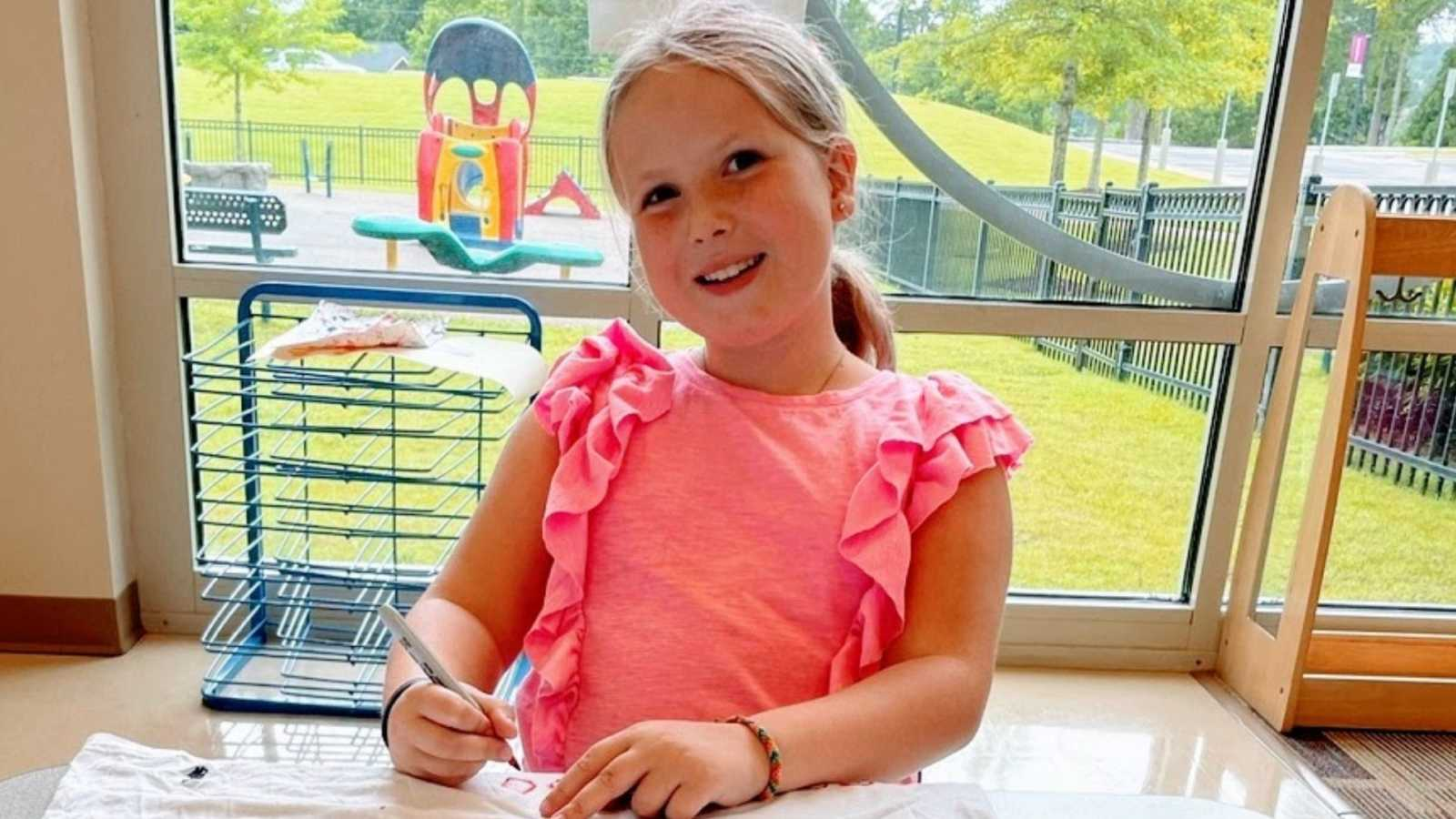 A young girl wearing a pink shirt sits at a table