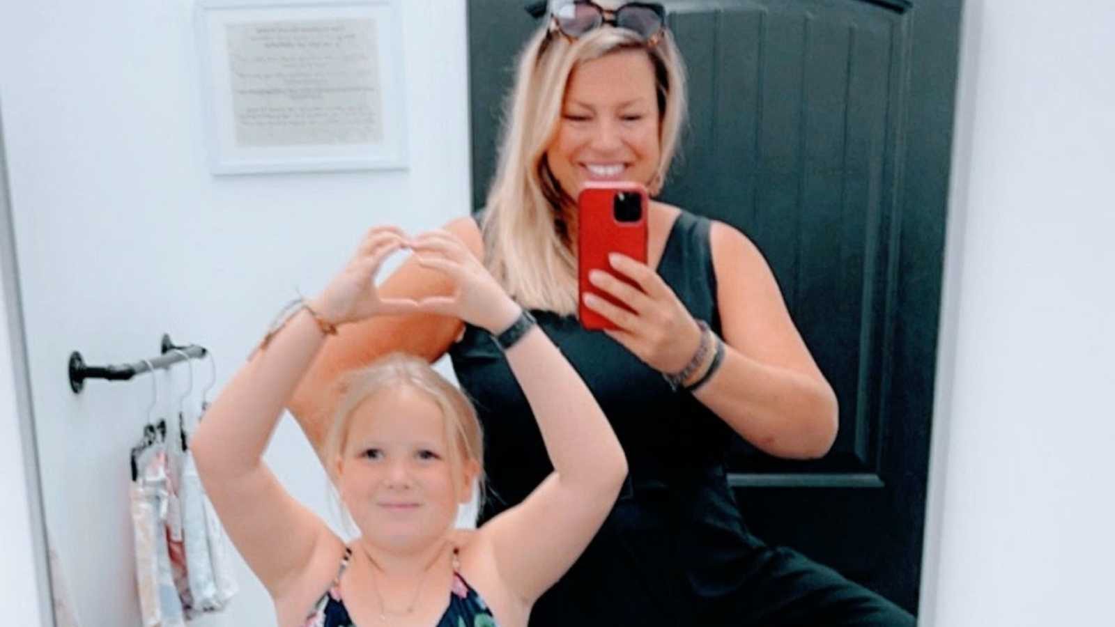 A woman takes a photo of herself and her daughter in a mirror