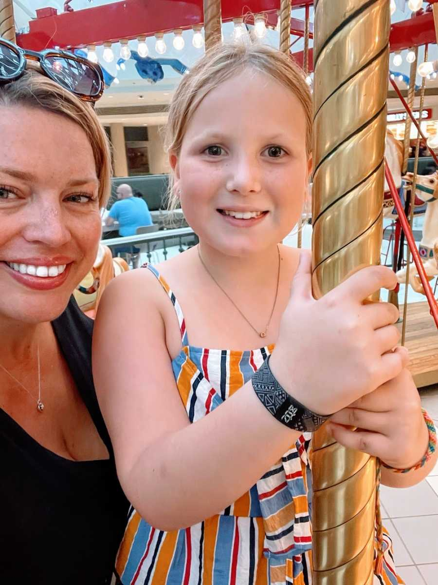 A woman and her daughter stand together on a carousel
