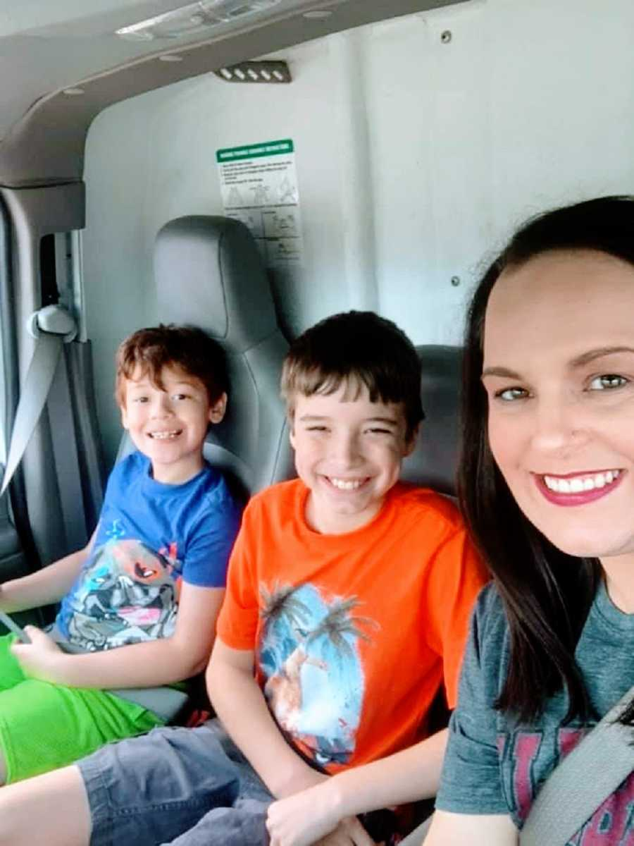 A mom sits in a truck with her two sons