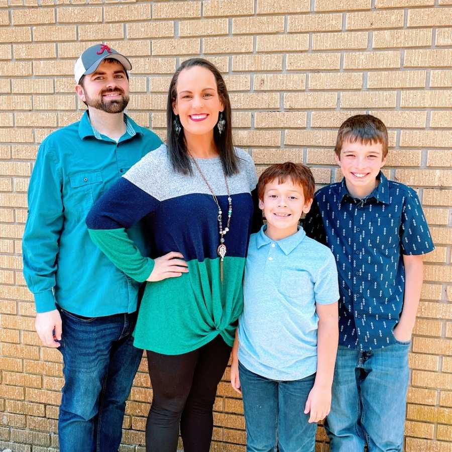A woman stands with her husband and two sons