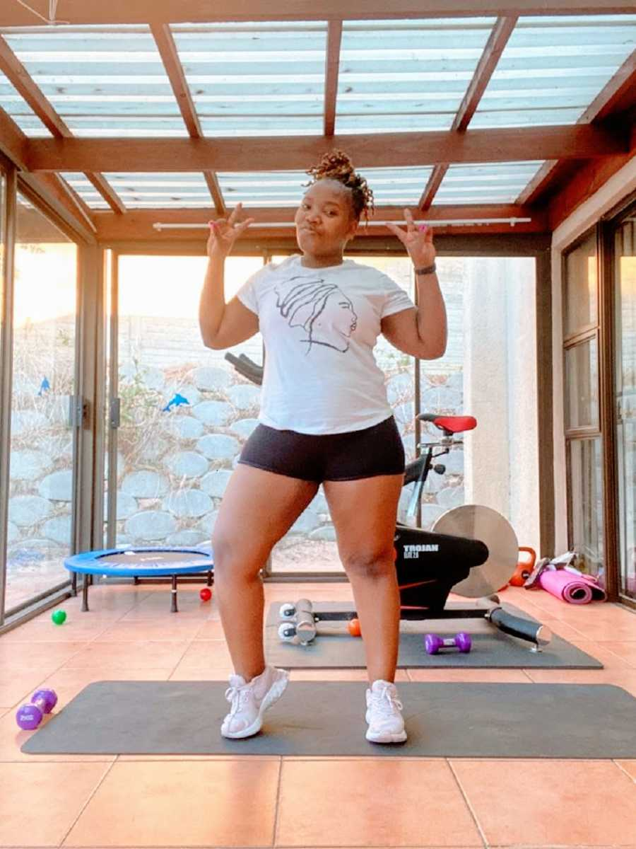 A woman stands in her home gym making peace signs