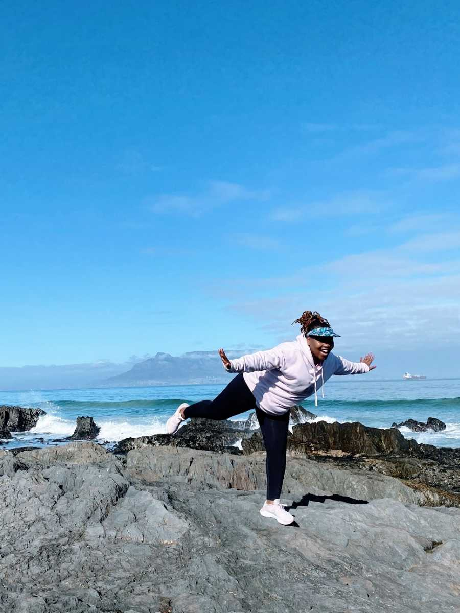 A woman balances on one foot by the ocean