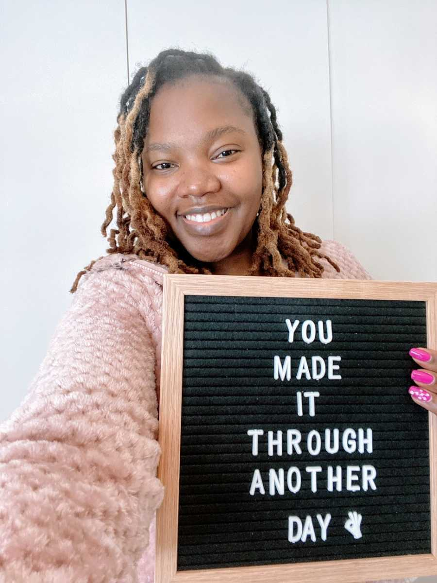"""A woman holds up a sign that says """"You made it through another day"""""""
