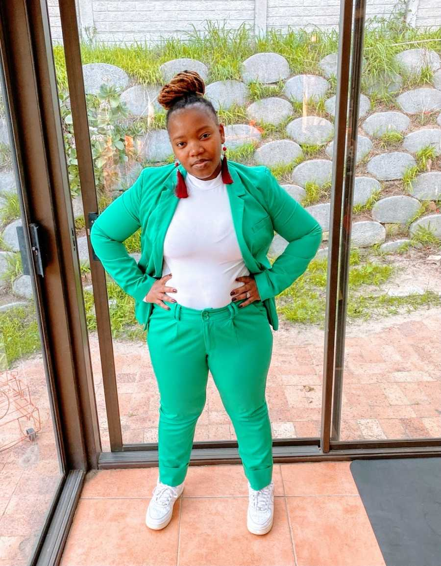 A woman stands in a green suit and pants with long earrings