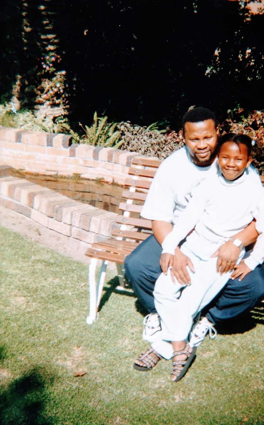 A young girl dressed in white sits with her father