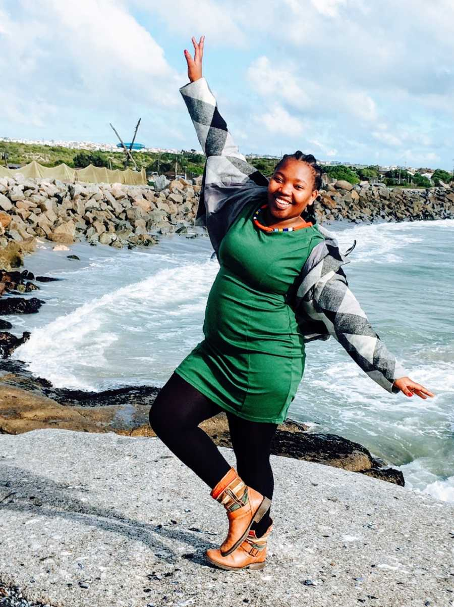 A woman wearing a green dress and a checkered jacket stands on one leg by the water