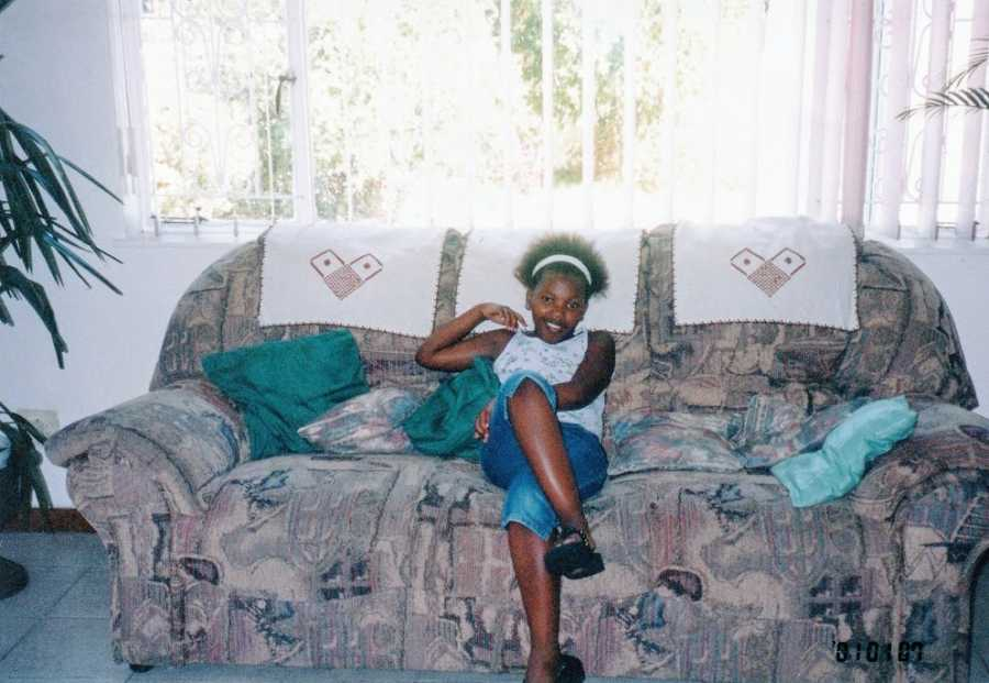A young girl sits alone on a floral couch